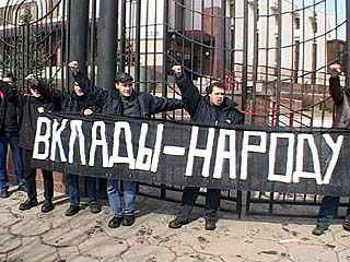 Группа молодых людей приковала себя наручниками к ограде Сбербанка